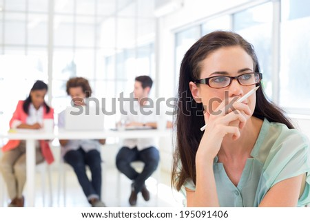 Attractive businesswoman contemplating while colleagues are in background in the office
