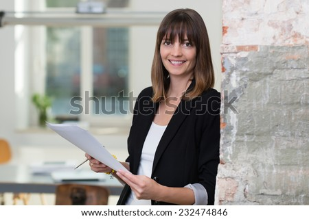 Attractive businesswoman dealing with paperwork leaning against a wall in the office holding a document in her hands smiling at the camera - stock photo