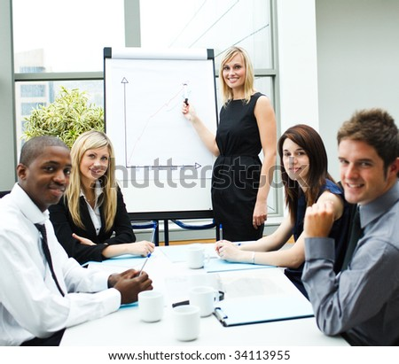 Attractive businesswoman giving a presentation to her team smiling at the camera - stock photo