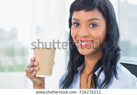 Attractive businesswoman holding coffee in office - stock photo