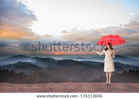 Attractive businesswoman holding red umbrella against epic mountain scenery - stock photo