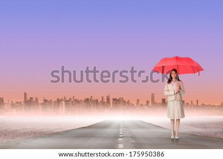 Attractive businesswoman holding red umbrella against road leading out to the horizon - stock photo