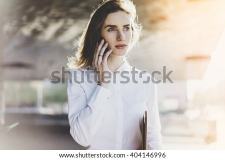 Attractive businesswoman in white shirt talking on her smart phone outdoors while working modern office or business center, flare light - stock photo