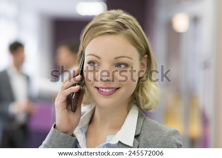 Attractive businesswoman on mobile phone in modern office - stock photo
