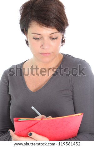 Attractive businesswoman or teacher holding a large red folder concentrating on writing notes isolated on white - stock photo