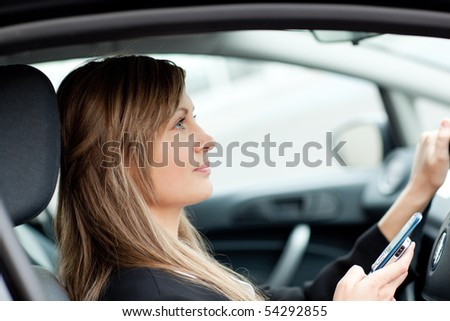 Attractive businesswoman sending a text while driving to work