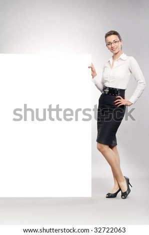 Attractive businesswoman showing empty white board - stock photo