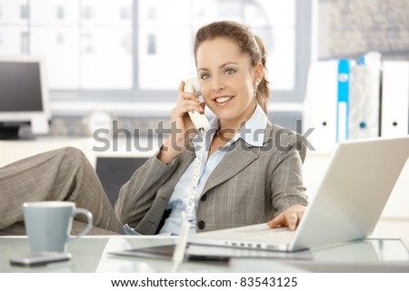 Attractive businesswoman sitting at desk, talking on phone, having laptop, smiling.? - stock photo