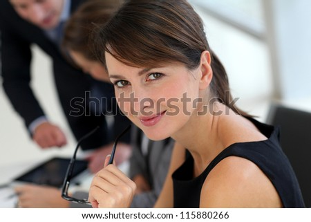 Attractive businesswoman sitting in office with workteam