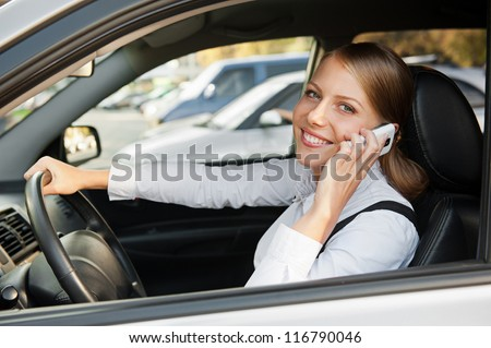 attractive businesswoman sitting in the car, talking on the phone and smiling