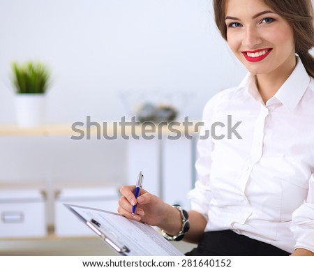 Attractive businesswoman sitting in the office. - stock photo