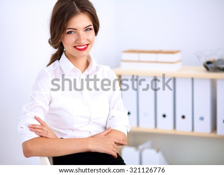 Attractive businesswoman sitting  in the office - stock photo