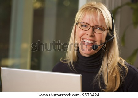 Attractive businesswoman smiles as she talks on her phone headset. - stock photo