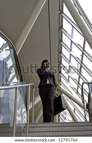 Attractive businesswoman smiling and talking on her phone as she stands at the top of the stairs