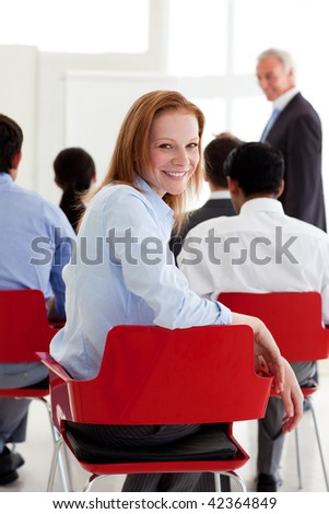 Attractive businesswoman smiling at the camera at a conference - stock photo