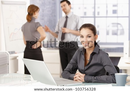 Attractive businesswoman smiling happily in office, sitting at desk, having laptop, colleagues chatting in background.