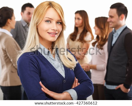 Attractive businesswoman smiling in a meeting with her colleagues and looking at camera .Business meeting concept. - stock photo