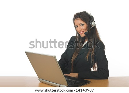 Attractive businesswoman, speaking on headset and smiling, typing on laptop computer