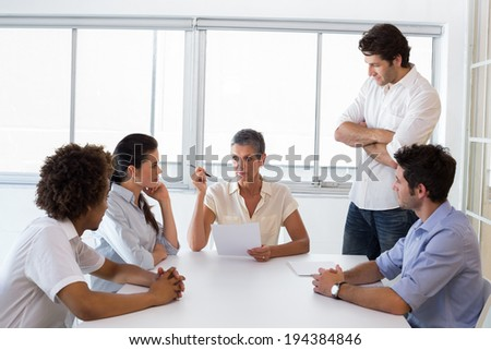 Attractive businesswoman speaking to her fellow coworkers on pressing matters - stock photo