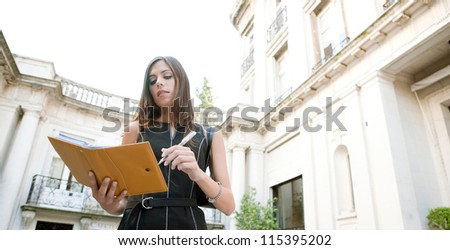 Attractive businesswoman standing in a luxury classic architecture coffee shop terrace, taking notes in her agenda. - stock photo