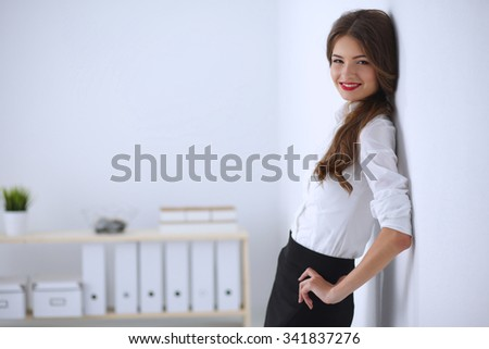 Attractive businesswoman standing in office - stock photo