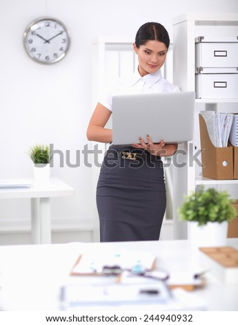 Attractive businesswoman standing in office with laptop - stock photo