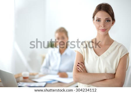 Attractive businesswoman standing near wall in office . - stock photo