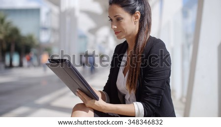 Attractive businesswoman standing on a waterfront promenade working on a tablet computer as she navigates the screen  profile view
