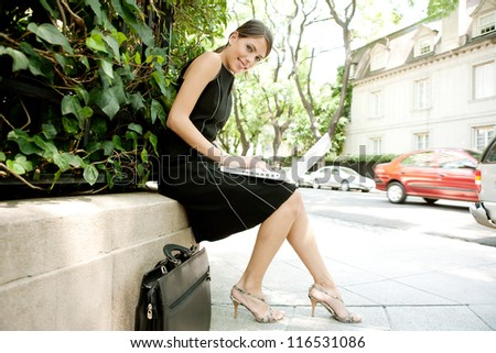 Attractive businesswoman using a laptop computer while sitting in a leafy city street during a sunny day, smiling.