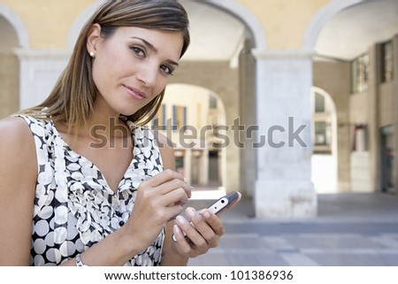 Attractive businesswoman using a smartphone in the city, smiling.