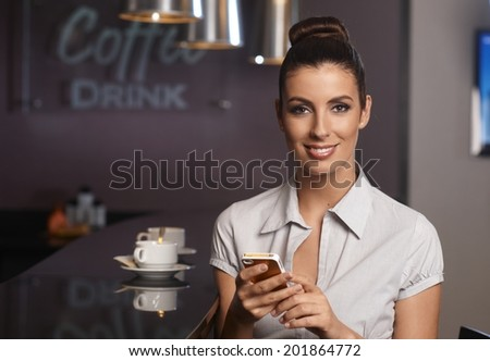 Attractive businesswoman using mobilephone, sitting in bar, smiling, looking at camera. - stock photo