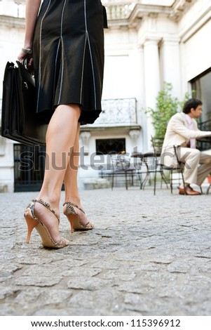Attractive businesswoman walking to a business meeting in a luxury coffee shop terrace, rear view of legs.