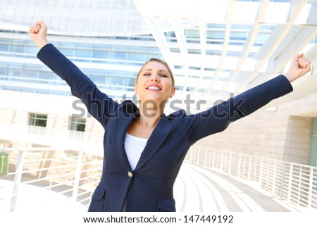 attractive businesswoman with her arms raised - stock photo