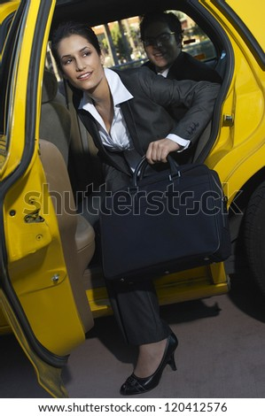 Attractive businesswoman with male colleague getting out of taxi - stock photo