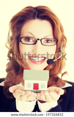 Attractive call center support woman with headset andhouse model in hands. Real estate concept.