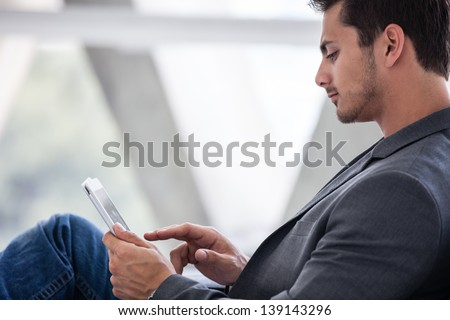 Attractive casual business man in his 20s working on a  think pad - stock photo