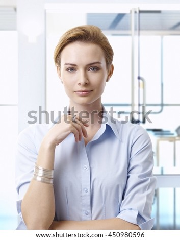 Attractive casual caucasian blonde business advisor at creative office, smiling, looking at camera, wearing jewelry. - stock photo