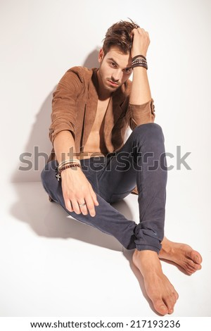 Attractive casual man posing against a brick wall, holding his hands on the wall, looking at the camera - stock photo