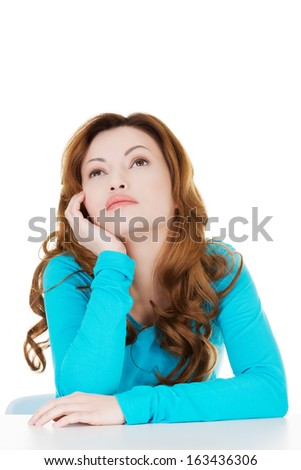 Attractive casual woman sitting and proping her head. Isolated on white.  - stock photo