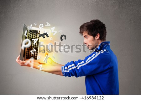 Attractive casual young man hoding notebook with colorful letters - stock photo