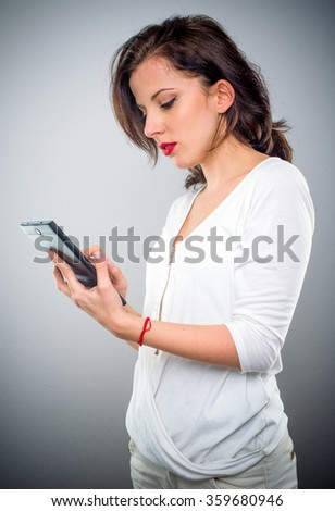 Attractive casual young woman checking her mobile phone for text messages looking at the screen with a serious expression, upper body side view on grey - stock photo