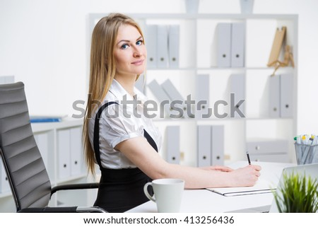 Attractive caucasian businesswoman sitting at office desk and writing - stock photo