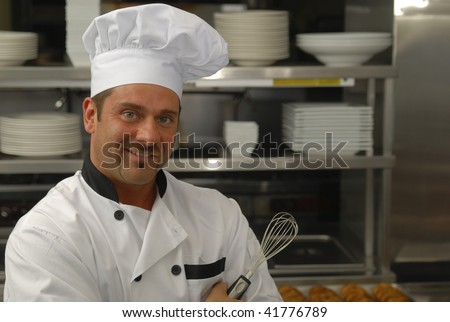 Attractive Caucasian chef holding a whisk in a restaurant kitchen. - stock photo