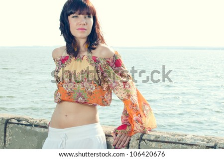 Attractive caucasian female posing near the shore during summer time - stock photo