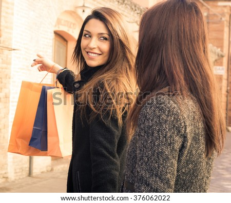 Attractive caucasian girl is pointing to her friend with his finger the next store to shop - caucasian people - people and shopping concept - stock photo