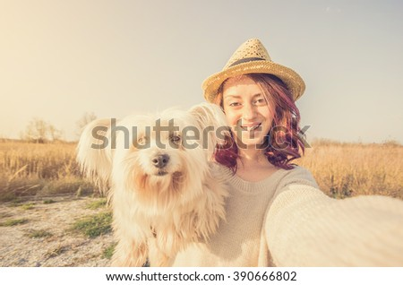 Attractive caucasian girl is taking a selfie with her dog in the countryside - caucasian people - people, animal, lifestyle, nature and technology concept - stock photo