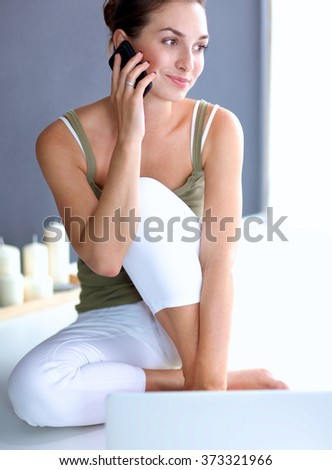 Attractive caucasian girl sitting on floor talking on the phone