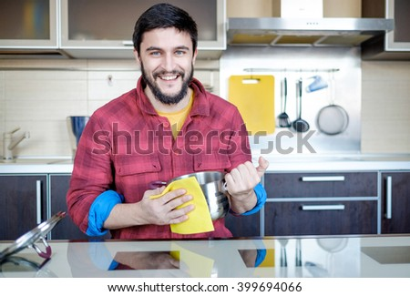 Attractive caucasian man cleaning the pot in the kitchen - stock photo