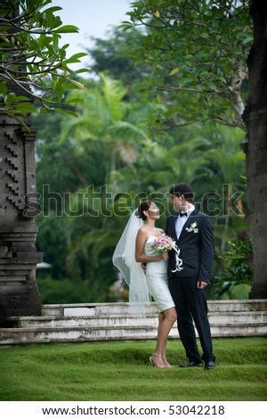 Attractive caucasian newly weds getting married outdoors in a garden - stock photo