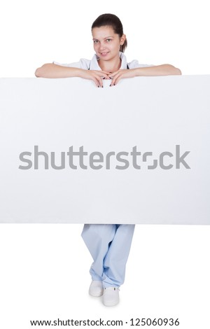 Attractive charming young female doctor or nurse with blank white signboard with copyspace peering around the side as she holds it up - stock photo